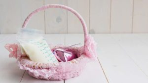 pink lace covered basket with a bag of baby formula in it