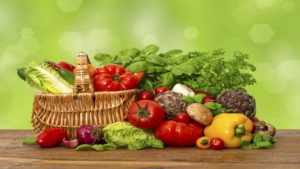 fresh vegetables and herbs over green background