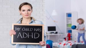 "woman holding small chalkboard saying ""My Child has ADHD"""