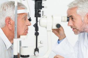 older doctor preforming eye exam on older patient