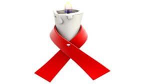 red ribbon tied around burning candle