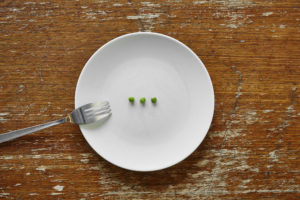 three peas on plate ready to be eaten malnutrition